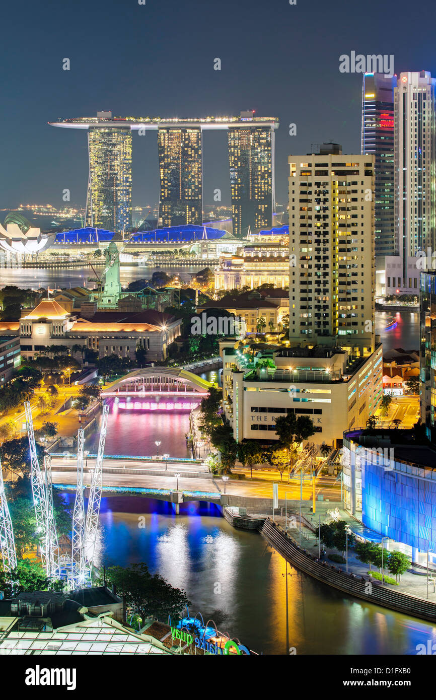 Elevated view over the Entertainment district of Clarke Quay, the Singapore River and city skyline at night, Singapore - Stock Image