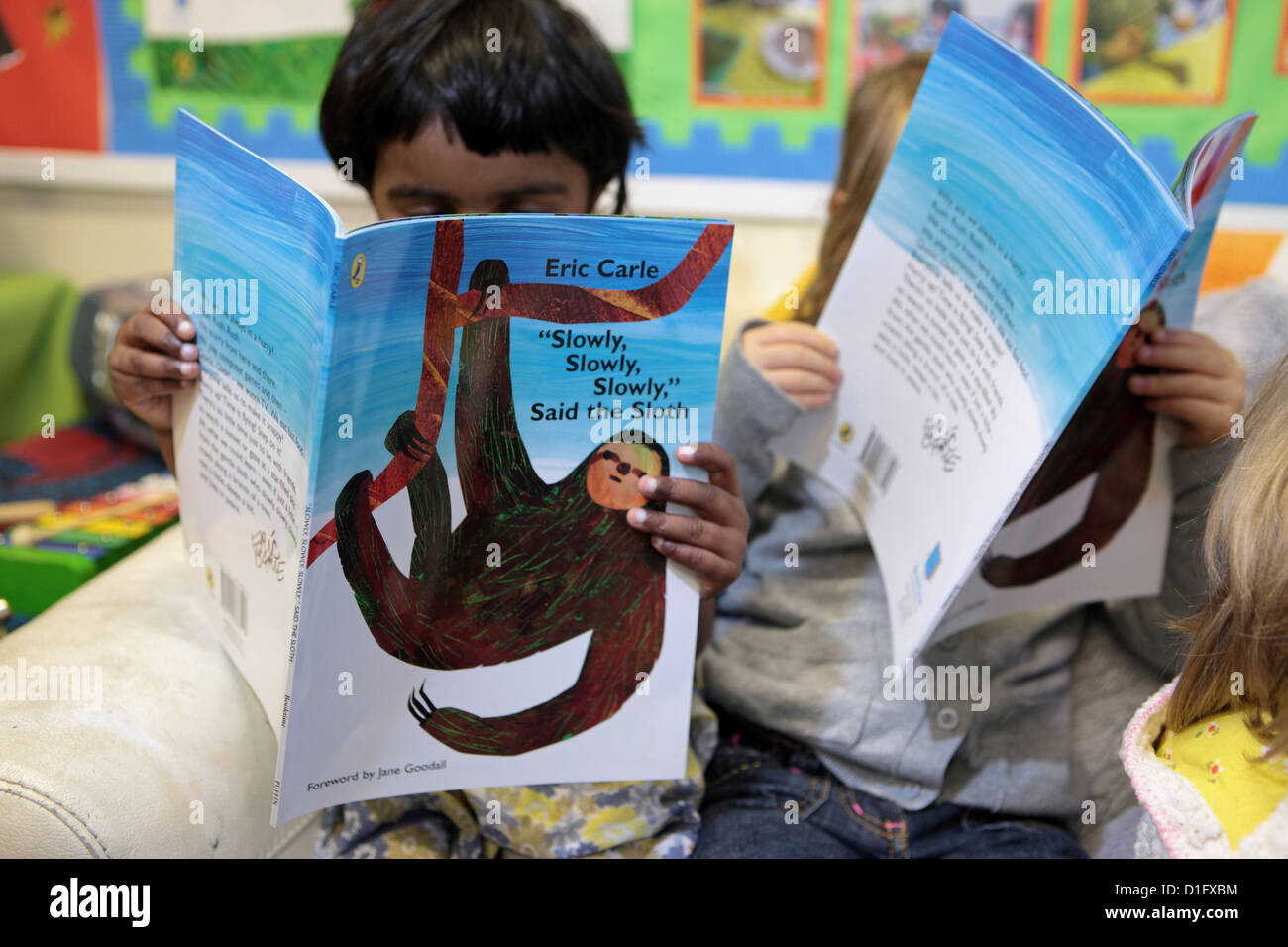 Two primary junior pupils girls engrossed in reading books, London, UK - Stock Image