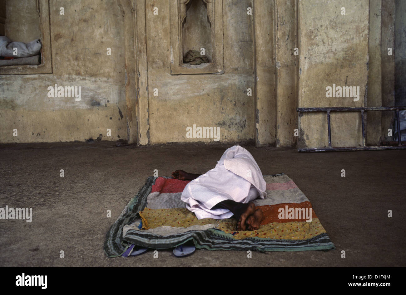 A homeless person sleeping in a mosque courtyard Bijapur Tamil Nadu India - Stock Image