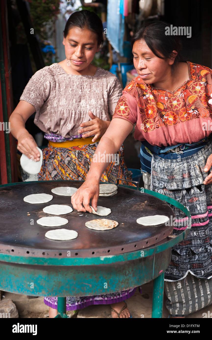 Mayan women baking tortillas in the market at Santiago Sacatepequez, Guatemala, Central America - Stock Image