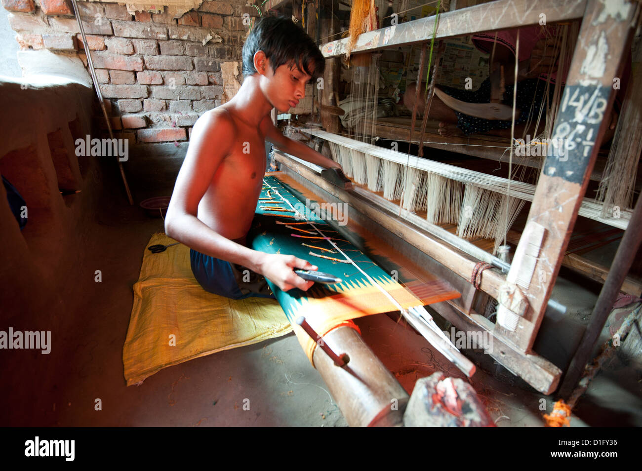 Young boy at loom weaving patterned silk sari using several spools of silk, Vaidyanathpur weaving village, Orissa, - Stock Image
