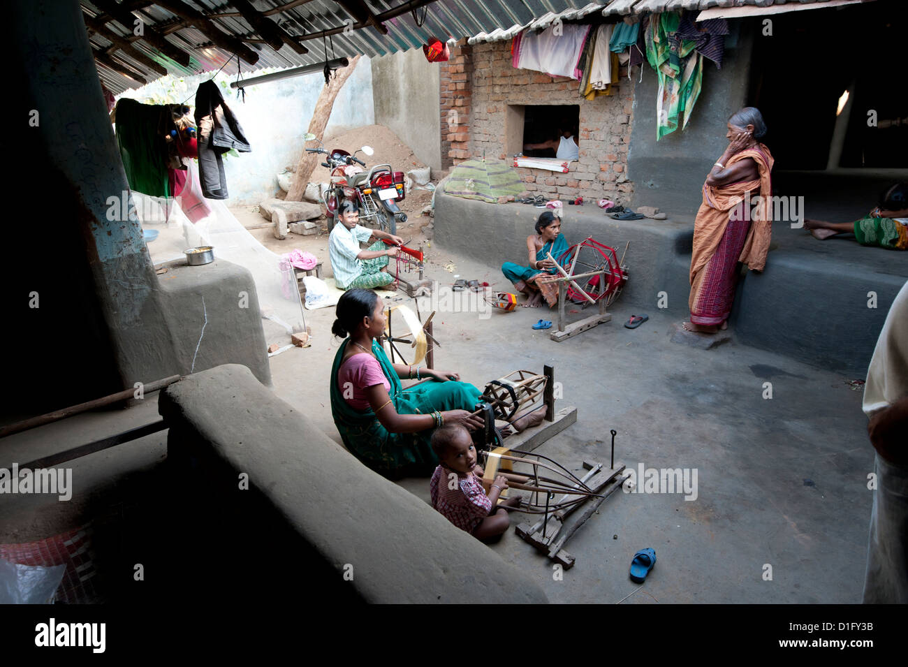 Women in communal back yard of weaving village, spinning silk thread, Vaidyanathpur weaving village, Orissa, India - Stock Image