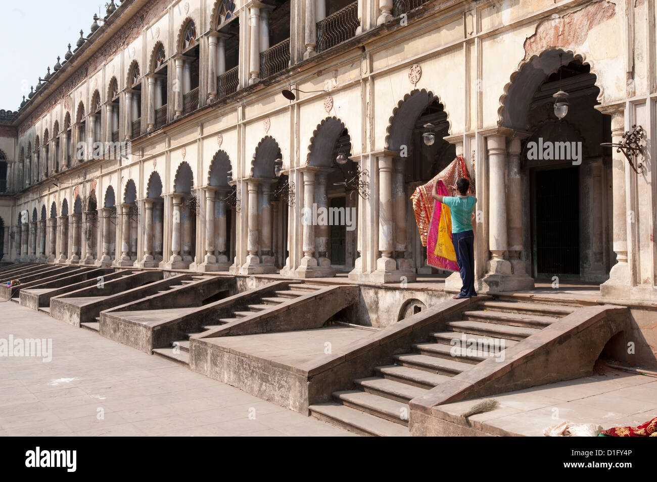 Man hanging out washed Quran cover cloths outside arched madrasa rooms in the Hugli Imambara, Hugli, West Bengal, - Stock Image
