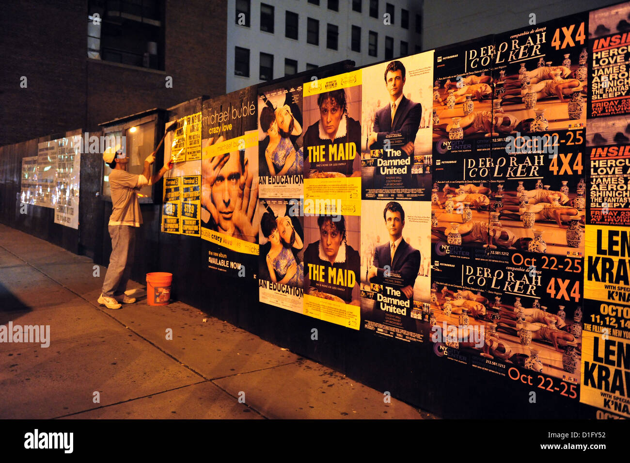 Man hanging poster on a street billboard on October 10 2009 in Manhattan New York. - Stock Image