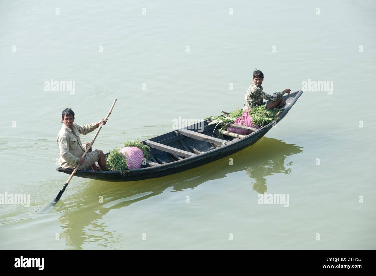 Men punting a wooden boat along the River Hugli, carrying bundles of alfalfa to market, near Kolkata, West Bengal, - Stock Image
