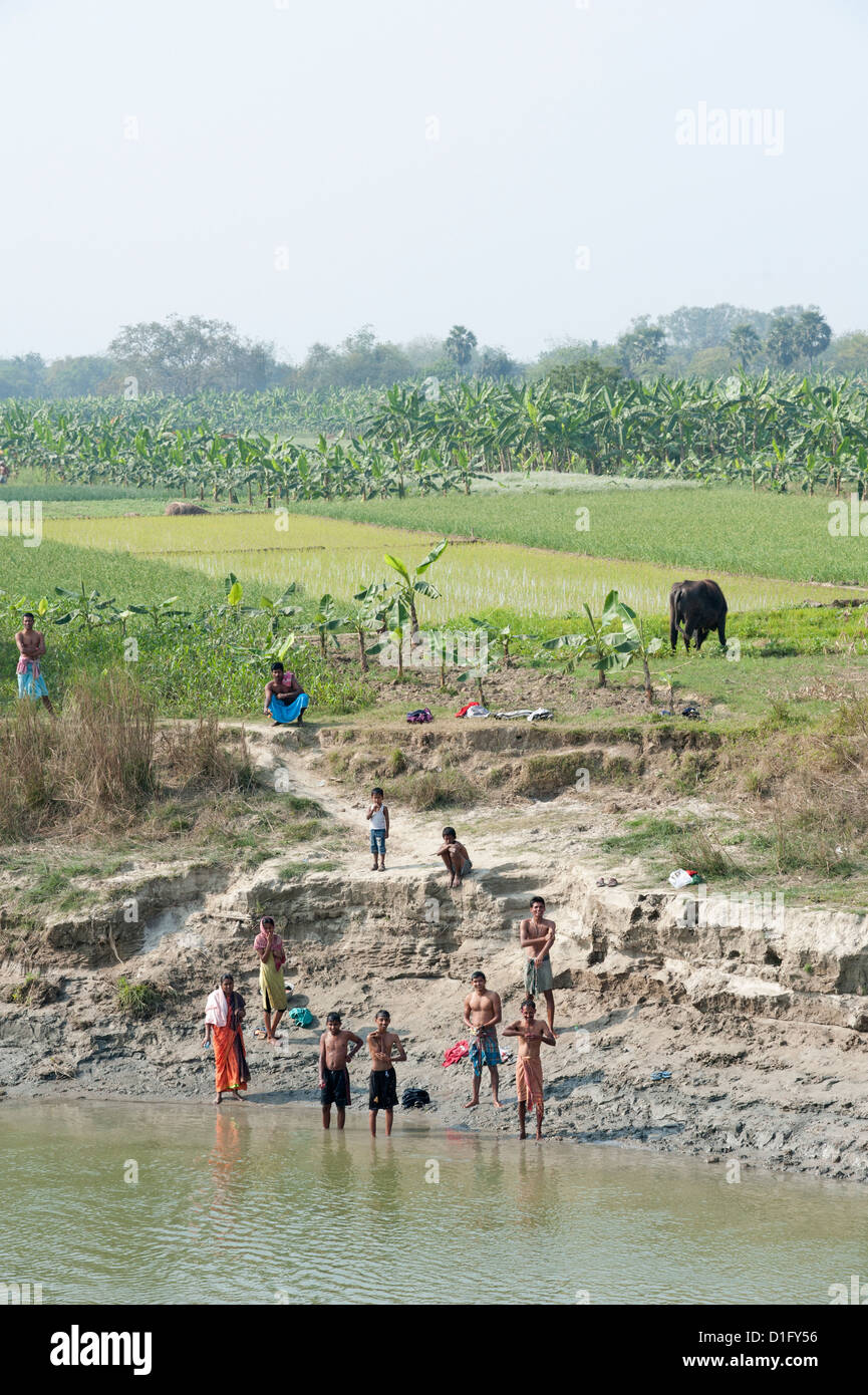 Men on the banks of the River Hugli after morning puja, near ricefields and banana paddy fields, rural West Bengal, - Stock Image