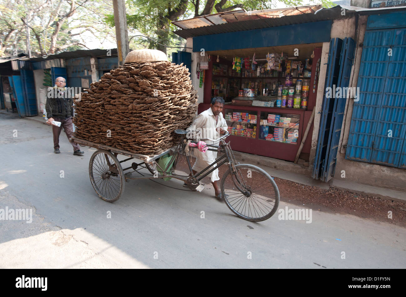Man wheeling cycle rickshaw laden with dung pats for use as domestic fuel, Hugli village, West Bengal, India, Asia - Stock Image