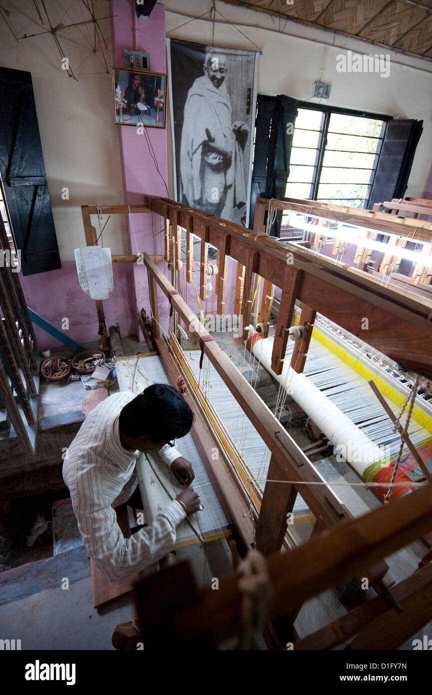 Man working a loom in a village weaving workshop beneath a large picture of Mahatma Gandhi, Kalna, West Bengal, - Stock Image