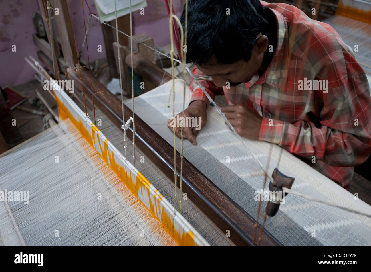 Weaver working in Ramdani method, using both domestic loom and needles, weaving undyed cotton lawn, Kalna, West - Stock Image
