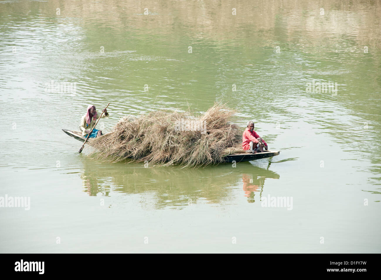 Boatmen paddling wooden boat laden with straw across the River Hugli (River Hooghly), rural West Bengal, India, - Stock Image