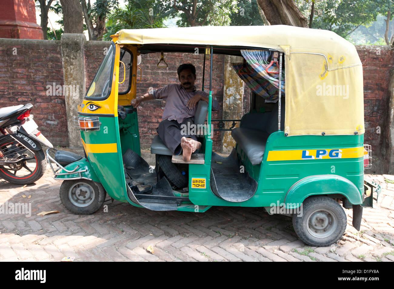 Rickshaw wallah waiting for custom in his rickshaw (tuk tuk), Barrackpore, West Bengal, India, Asia - Stock Image