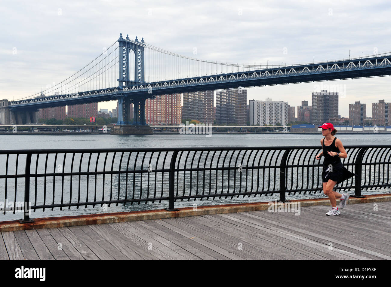 American woman runs under Manhattan Bridge on October 10 2009 in Manhattan New York. Stock Photo