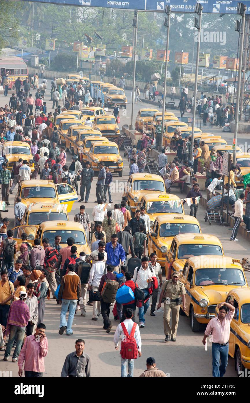 Yellow Kolkata taxis outside Howrah Railway Station in morning rush hour, Howrah, Kolkata (Calcutta), West Bengal, - Stock Image