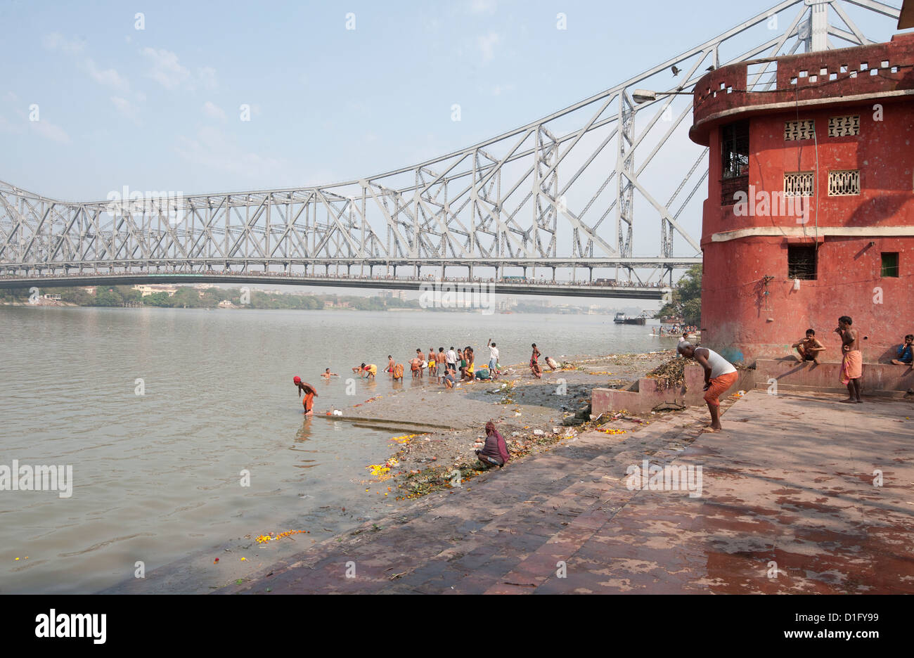 Men performing ablutions on ghats beneath the Howrah Bridge in the early morning, Kolkata (Calcutta), West Bengal, - Stock Image