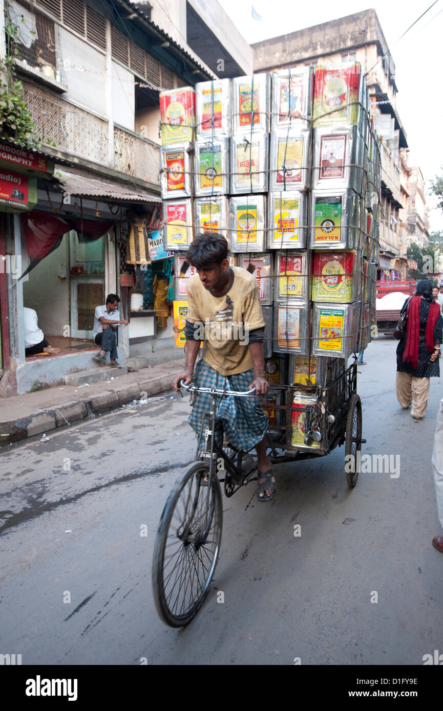 Cycle rickshaw carrying huge load of oil cans through market, Kolkata (Calcutta), West Bengal, India, Asia - Stock Image