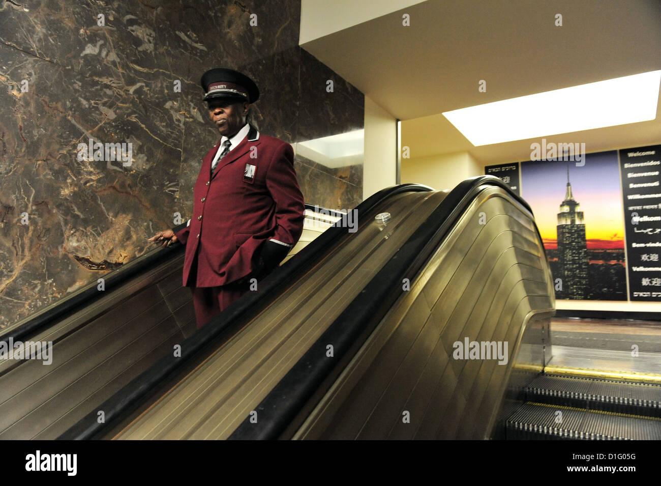 Hotel bellboy coming down in the escalator of the Empire State Building in Manhattan New York - Stock Image