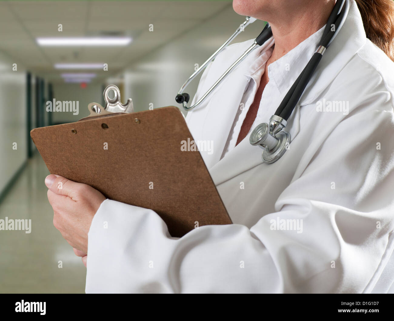 woman doctor with clipboard in hospital hall - Stock Image