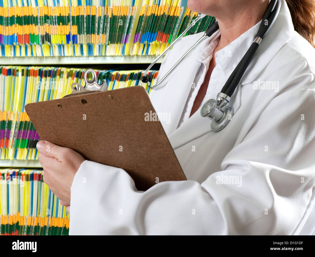 woman doctor with clipboard in medical records room - Stock Image