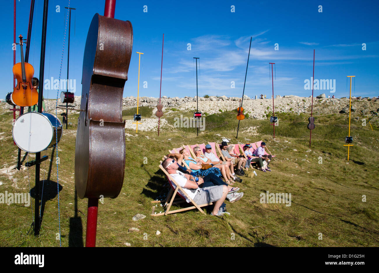 An audience in deck chairs listening to aeolian music from various instruments at Harmonic Fields on Portland Bill - Stock Image