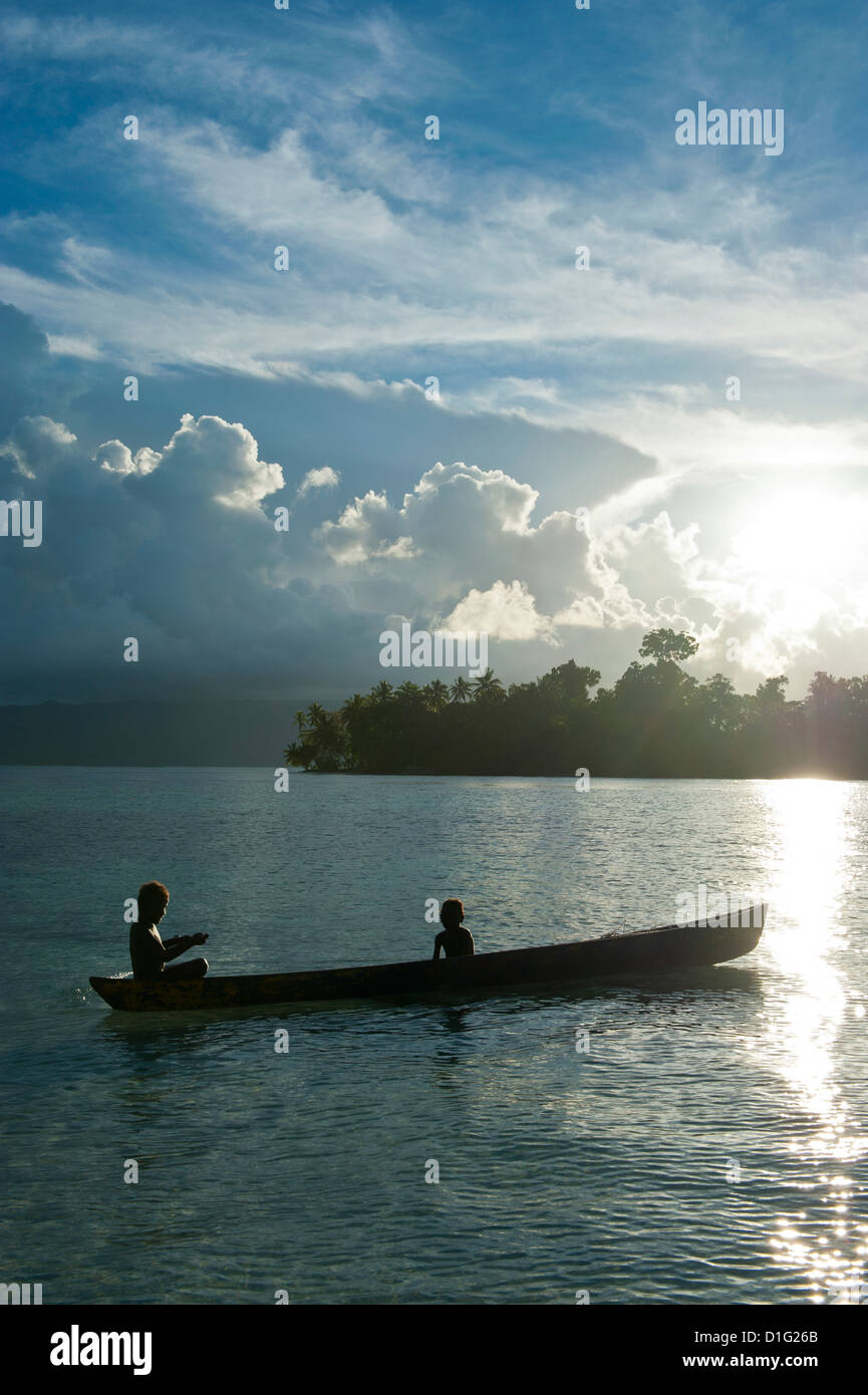 Boys in a canoe in backlit in the Marovo Lagoon, Solomon Islands, Pacific - Stock Image