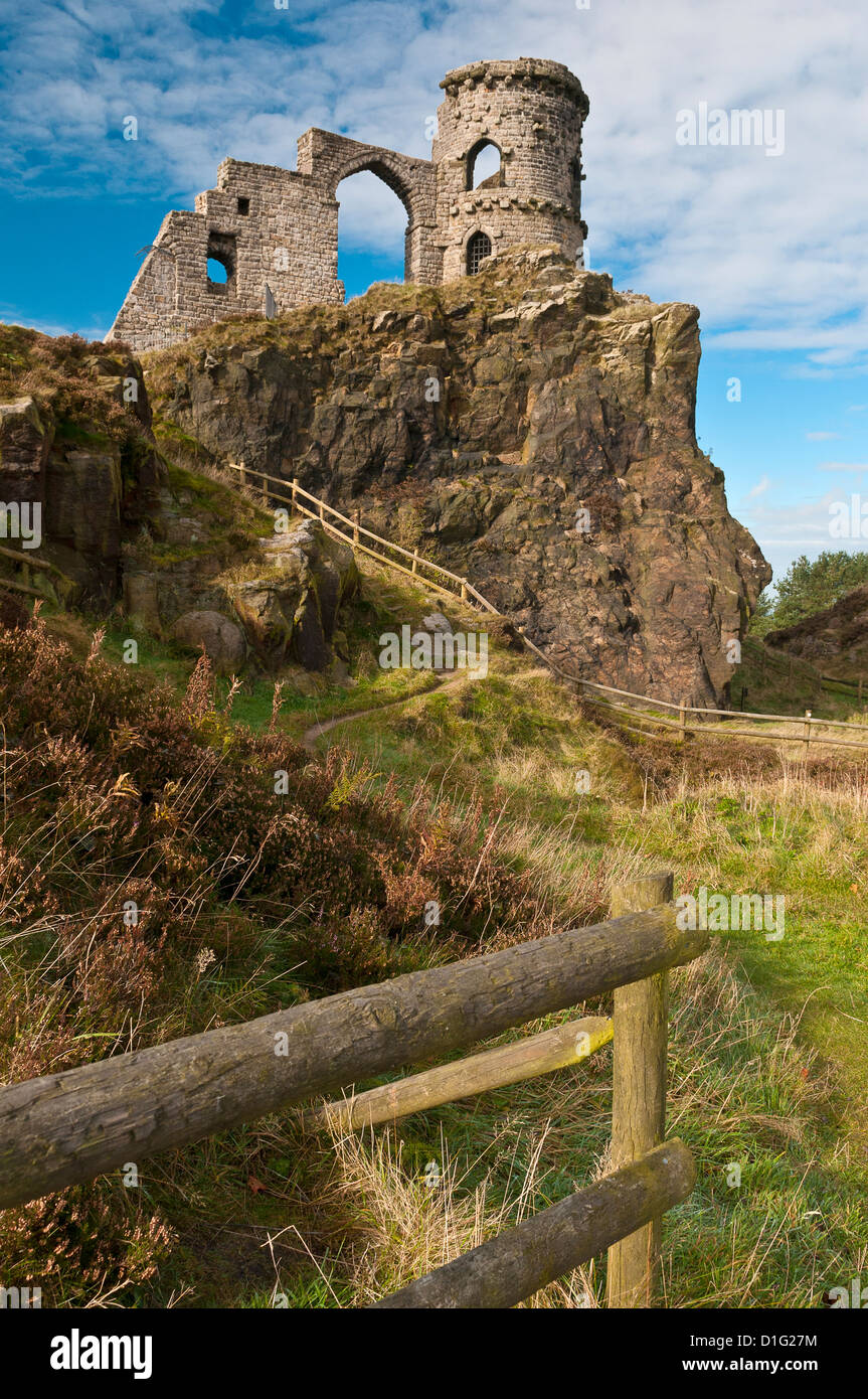 Mow Cop Castle, a folly on the Cheshire-Staffordshire border; fences and path in foreground; blue sky with white - Stock Image