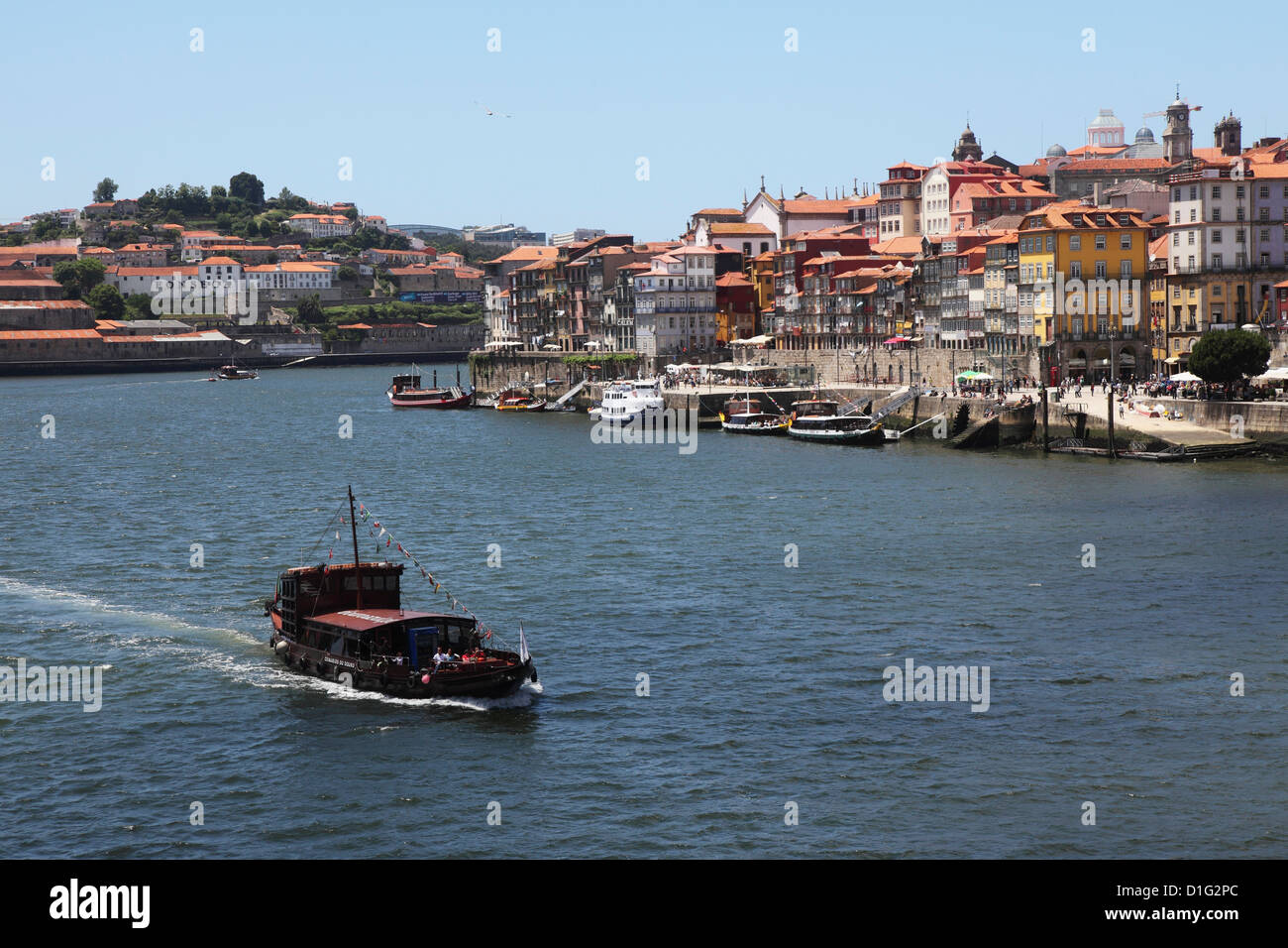 A boat cruises on the River Douro, past the Ribeira District, UNESCO World Heritage Site, Porto, Douro, Portugal, Stock Photo