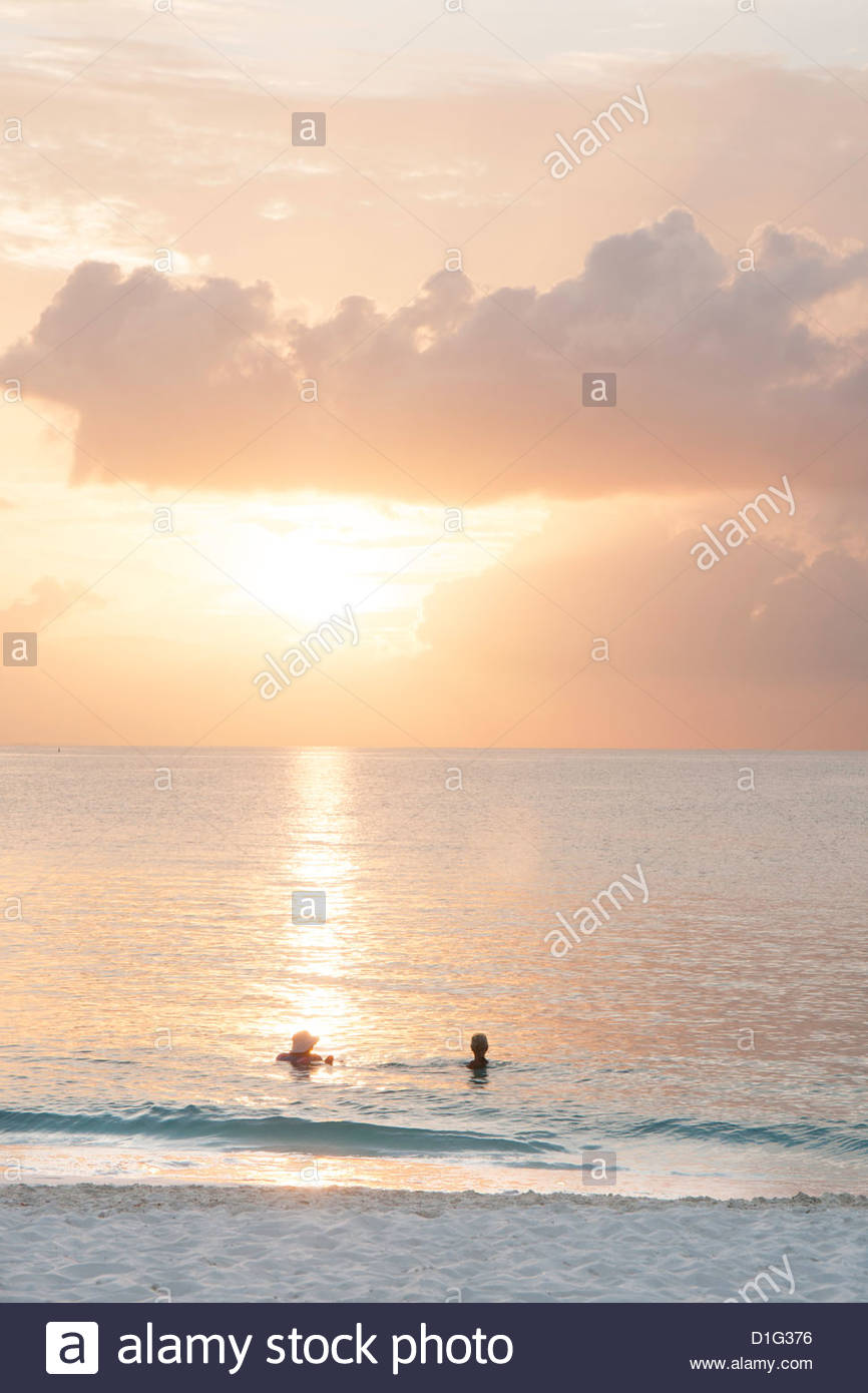 Two swimmers in ocean at sunset, Grace Bay, Providenciales, Turks and Caicos, West Indies, Caribbean, Central America - Stock Image