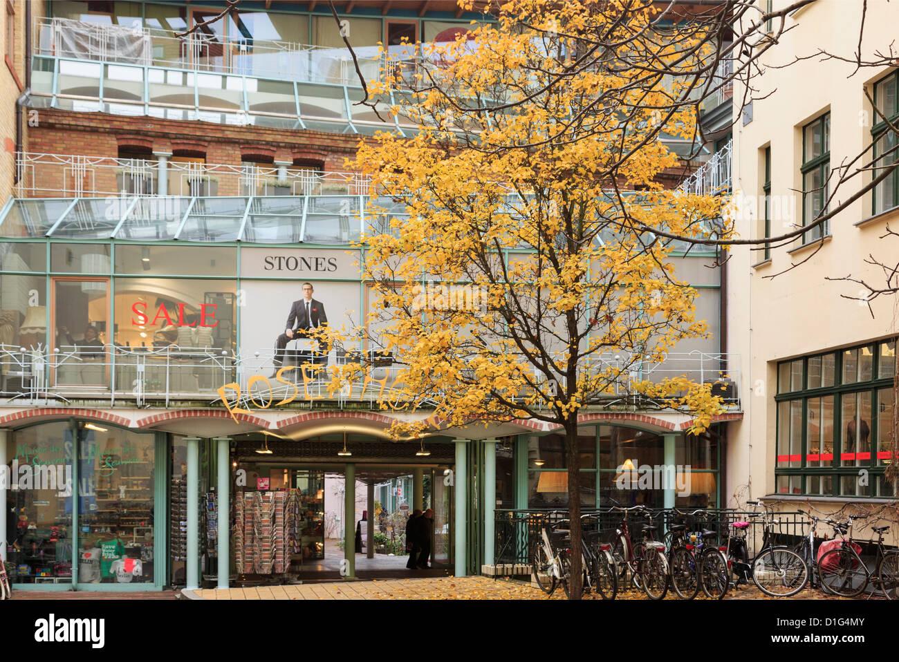 Trendy shops in the historic garden courtyards of Hackesche Hofe in former east Berlin, Germany - Stock Image