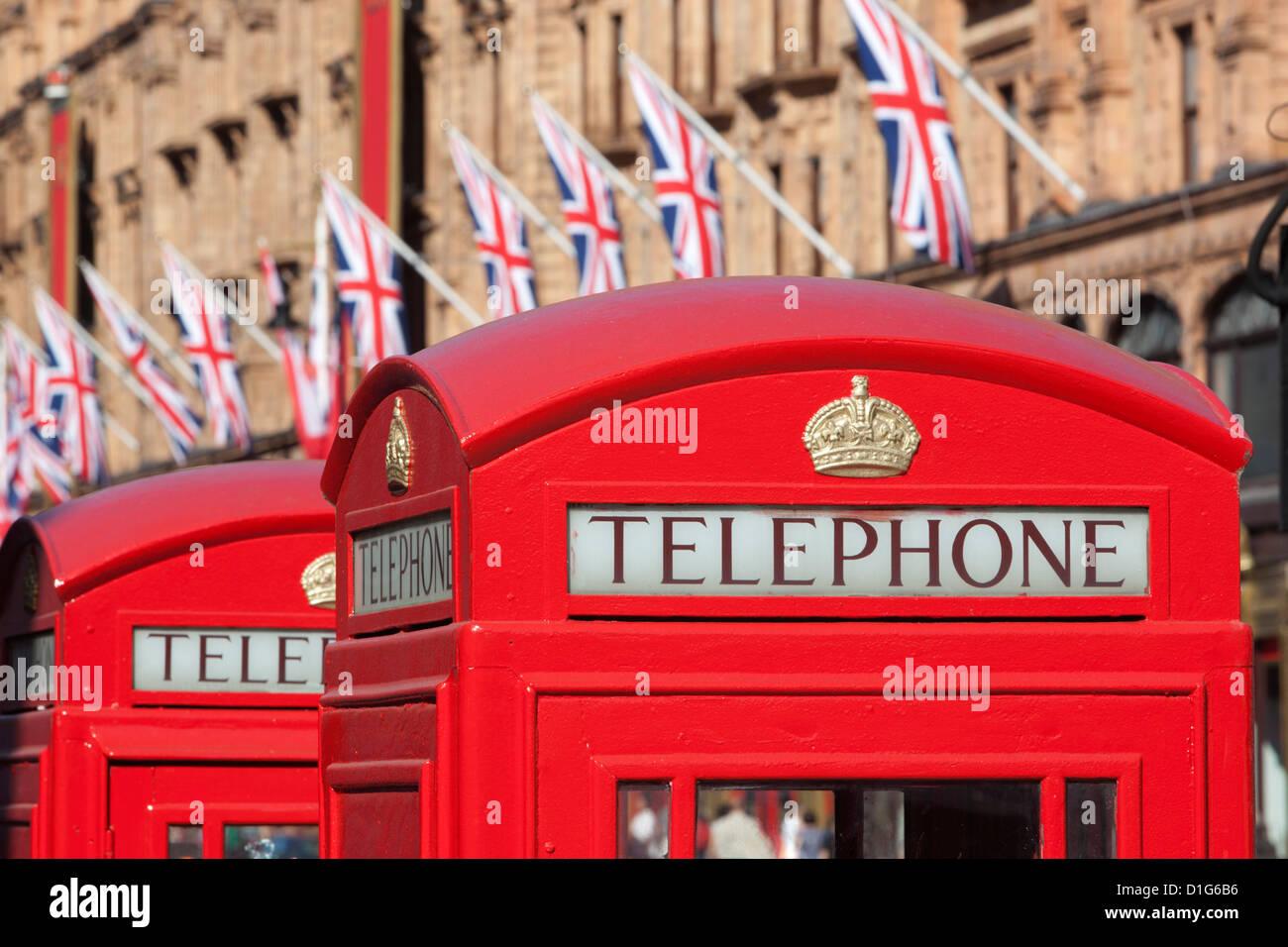 Red telephone boxes opposite Harrod's, Knightsbridge, London, England, United Kingdom, Europe - Stock Image