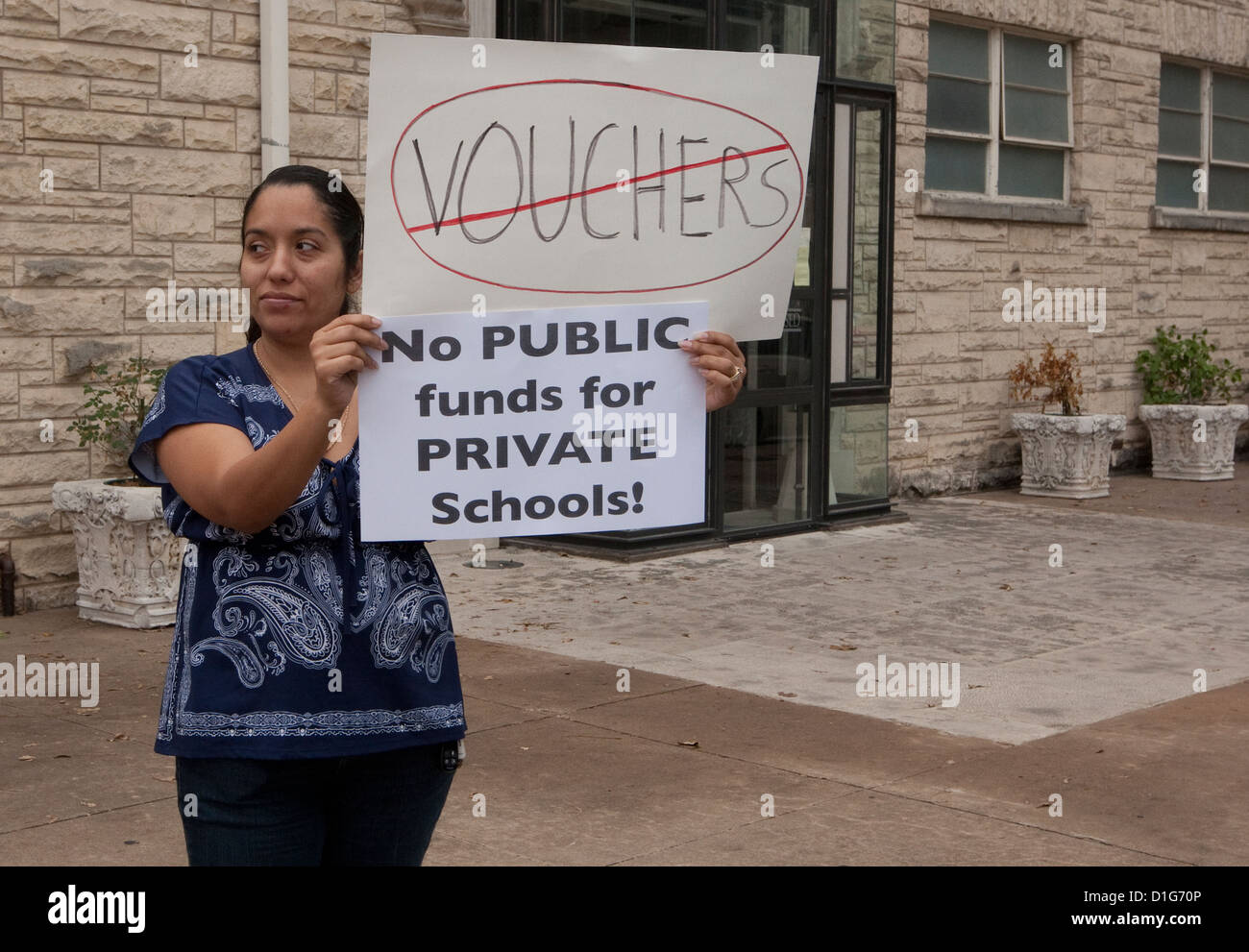 Hispanic female holds up sign in Texas protesting the use of public tax money to fund private schools including - Stock Image