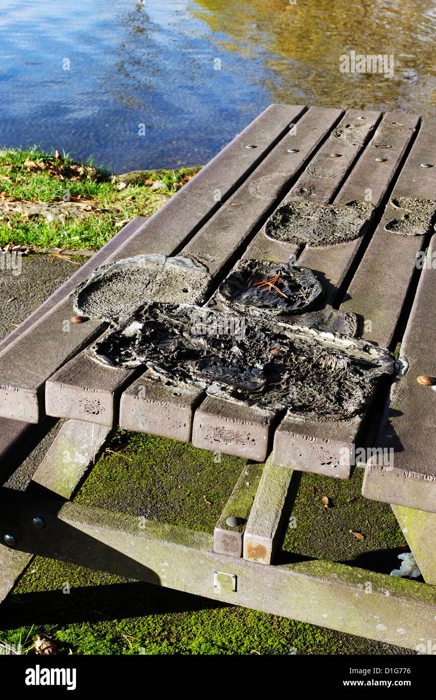 Damage caused to picnic table by the thoughtless use of Barbecues. - Stock Image