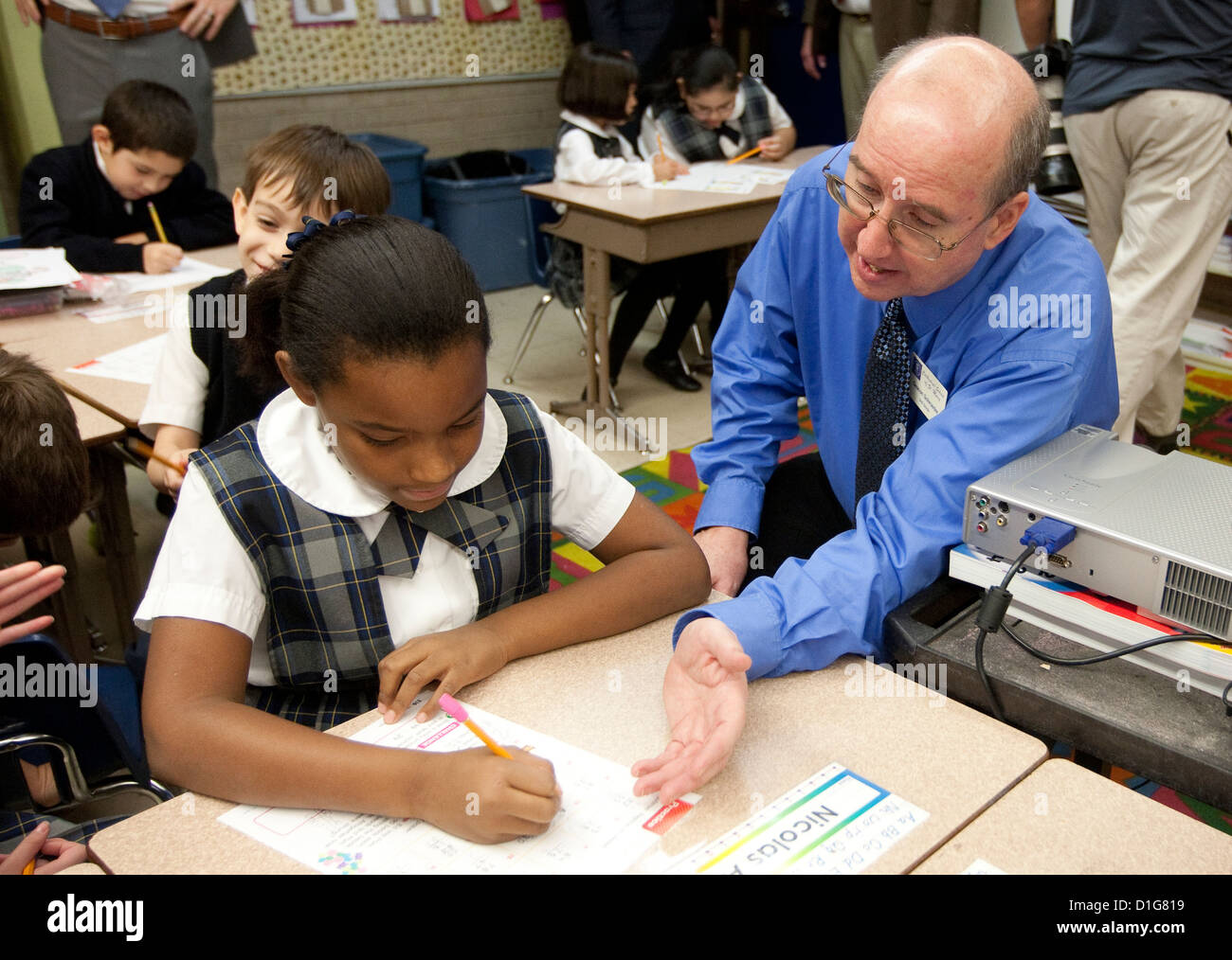 White male teacher assists African-American and Anglo students wearing uniform at private Catholic elementary school - Stock Image