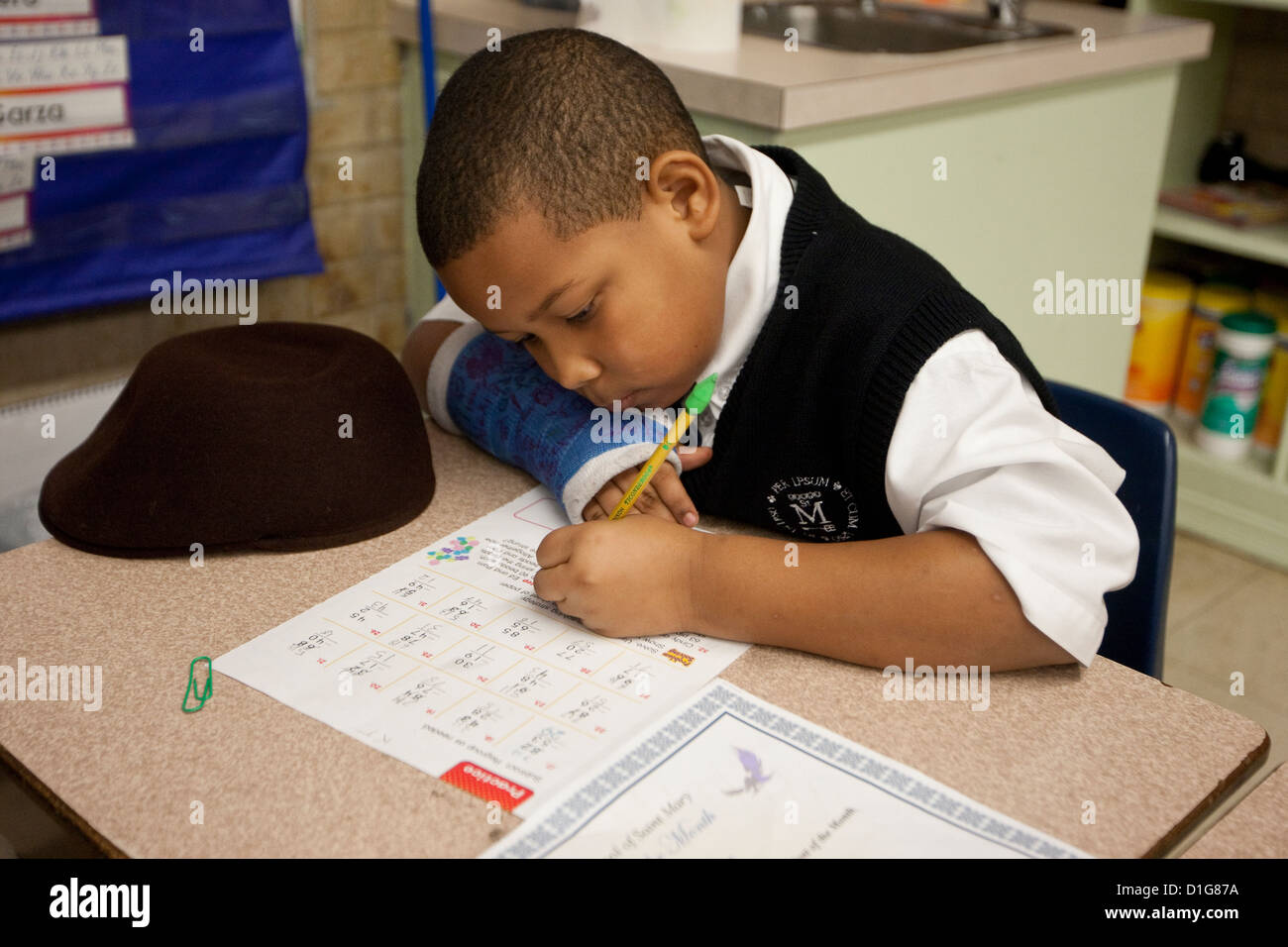 African-American boy in second grade elementary private Catholic school in Texas does school work at desk in classroom - Stock Image