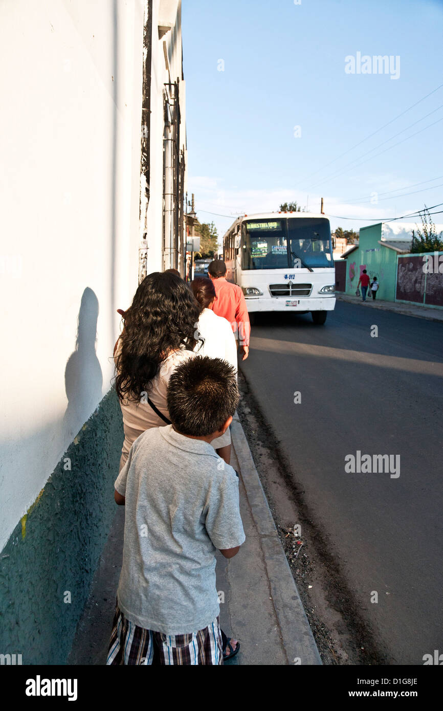 people waiting for approaching city bus on narrow sidewalk of Calle Cuauhtemoc Oaxaca de Juarez Mexico - Stock Image