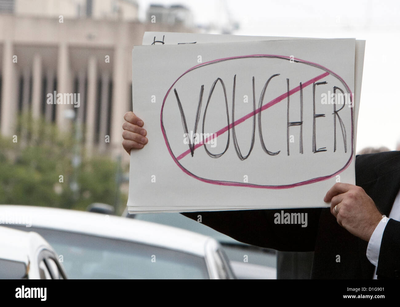 man holds up sign protesting school voucher use in Texas where lawmakers may allow use of public tax funds for private - Stock Image
