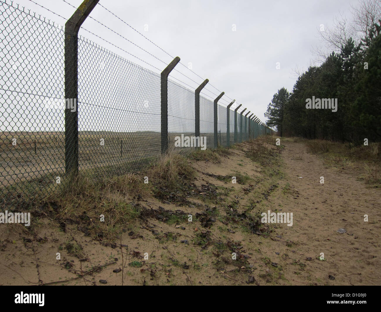 Wire security fence around an empty plot of land, near Swansea, South Wales, December 2012 - Stock Image