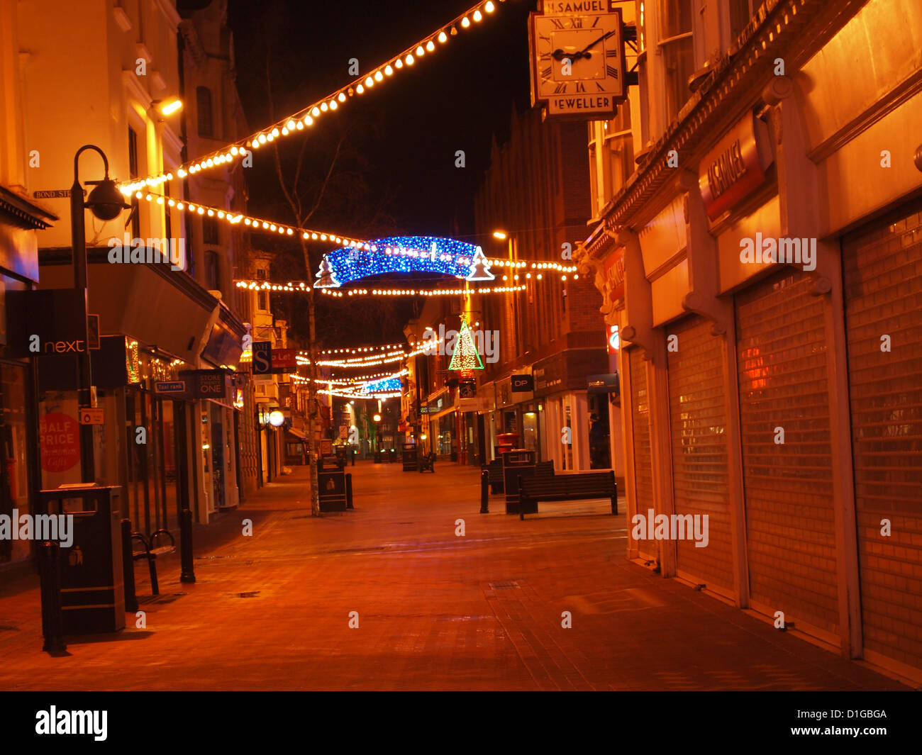 Deserted high street at night with Christmas lights in Weymouth, Dorset UK - Stock Image