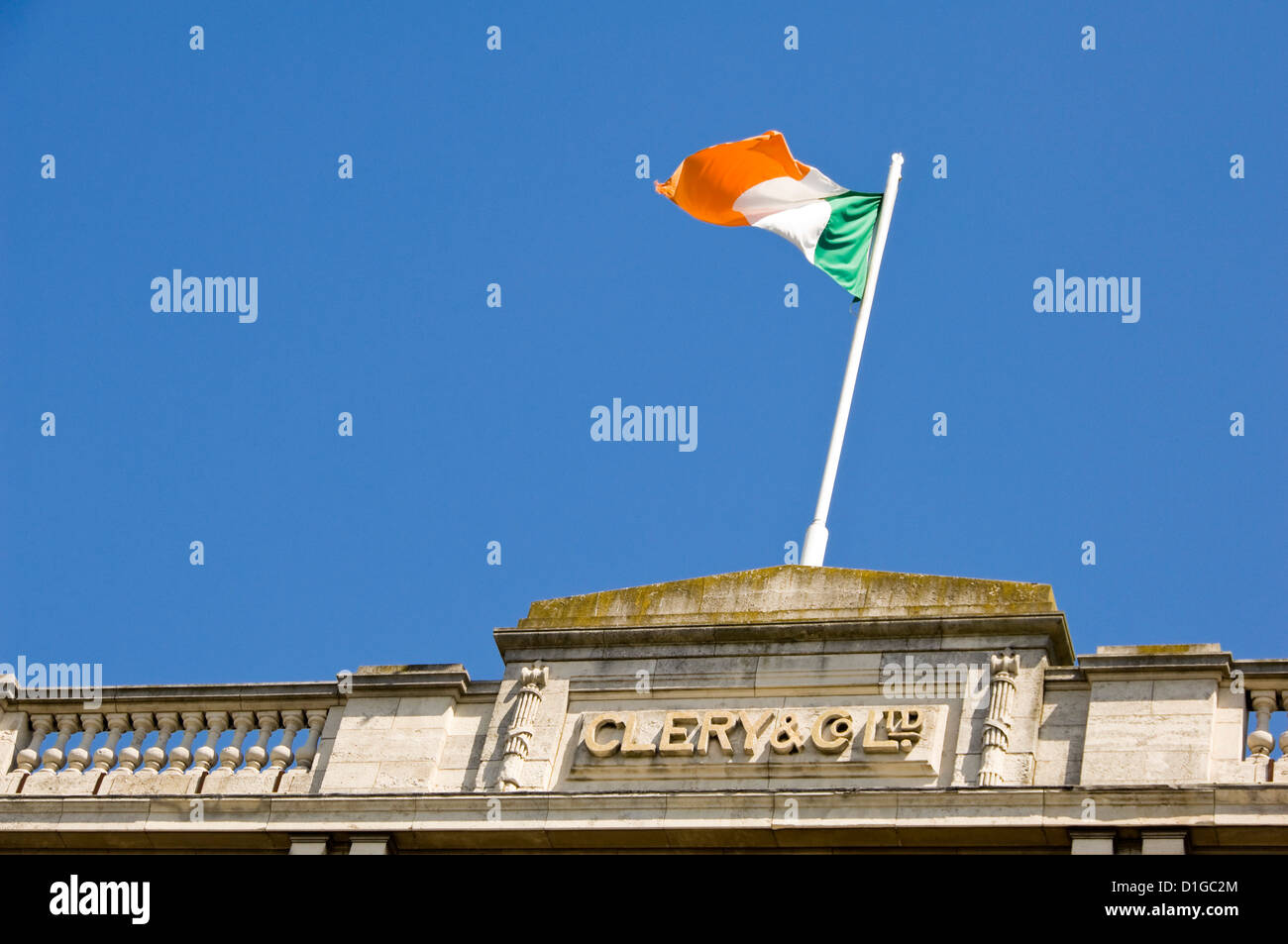 Horizontal view of the Irish national flag flying high above Clery & Co department store in Dublin. Stock Photo