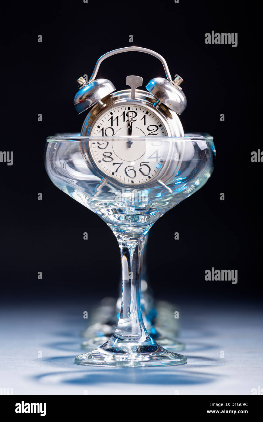 Alarm clock in an empty champagne glass showing twelve o'clock hour. - Stock Image