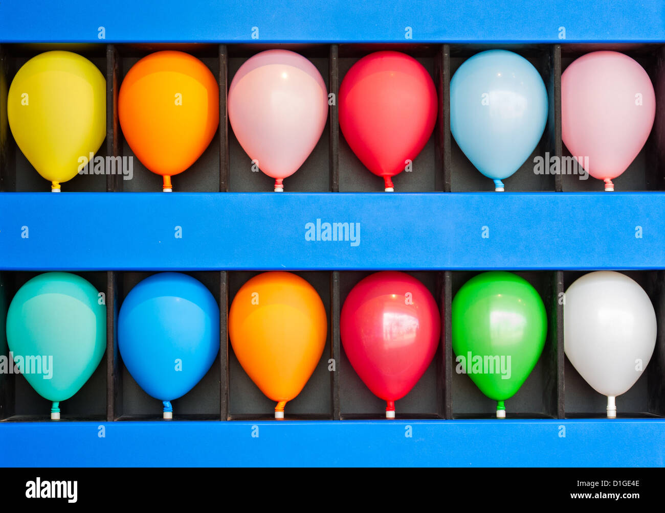 A blue wall case with colorful balloons. Photo is of a boardwalk arcade game. Only the case and balloons are shown. - Stock Image