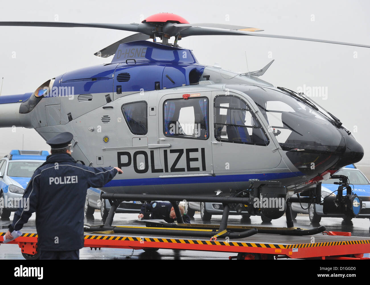 A police officer walks past the new EC 135 helicopter at the airport in Dresden, Germany, 19 December 2012. Saxony's - Stock Image