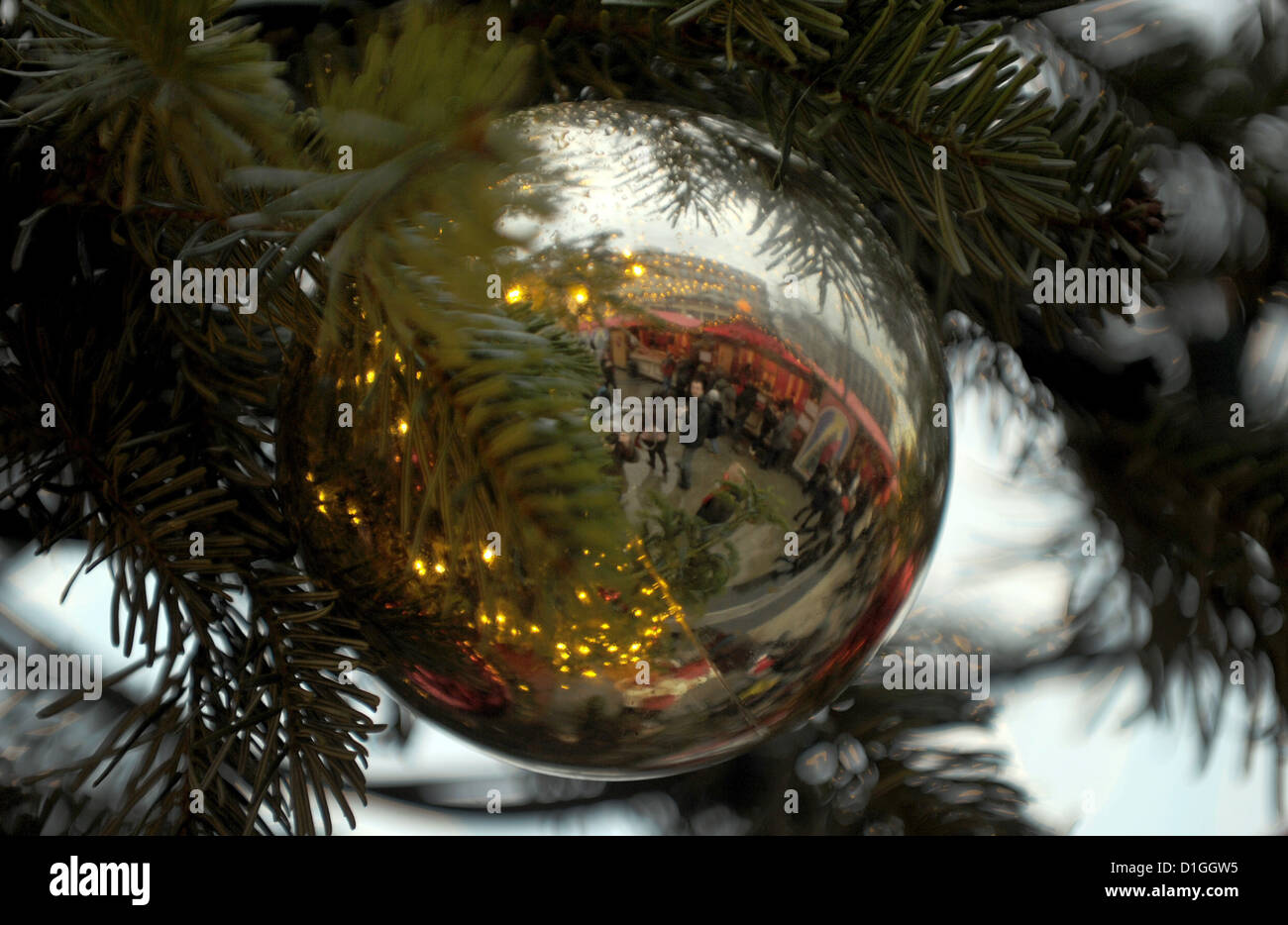 The reflection of passing visitors appears on a christmas tree bauble on the Christmas market in Cologne, Germany - Stock Image