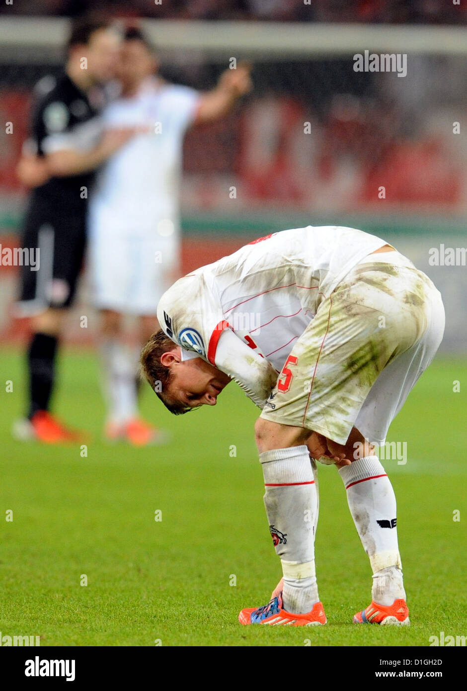 Cologne's player Daniel Royer bends forwards taking a deep breath as he stands on the pitch following the DFB - Stock Image