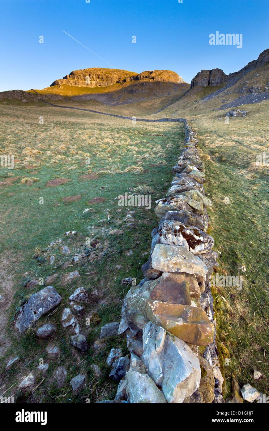 Drystone wall beneath Attermire Scar at sunrise, Settle, North Yorkshire, Yorkshire, England, United Kingdom, Europe - Stock Image