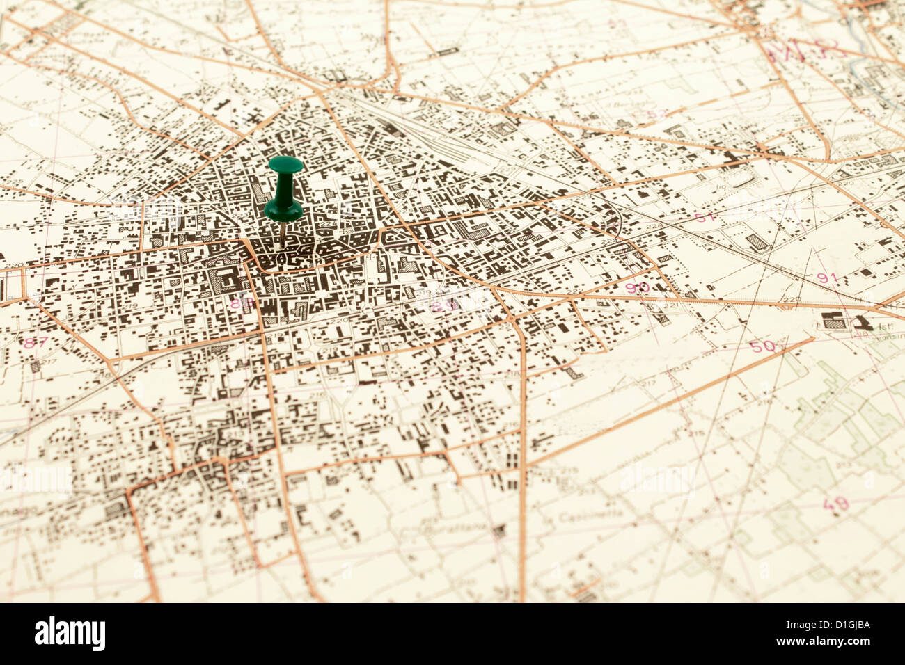 Thumbtack marks the center of an old city map. - Stock Image