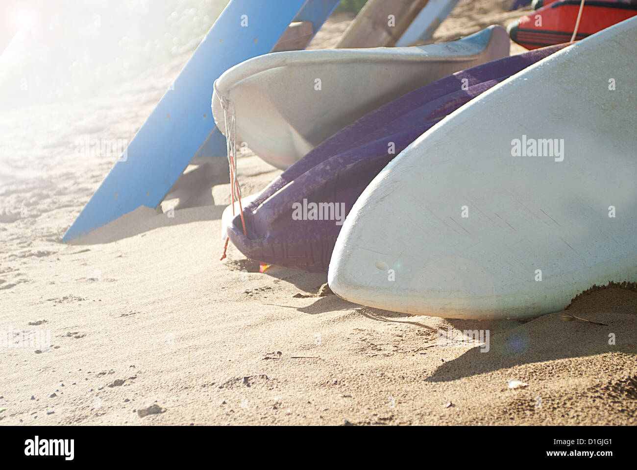 Three surf boards resting in the sand with the sunshine - Stock Image