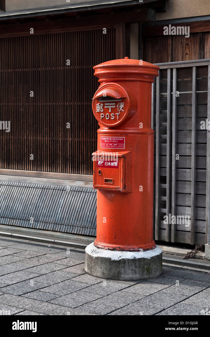 Gion, Kyoto, Japan. A pillarbox or postbox stands in front of a traditional wooden building - Stock Image