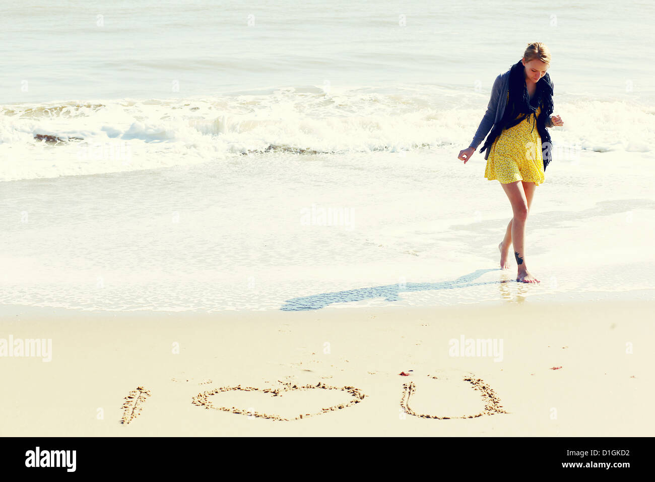 Young woman on a sunny beach with 'I Love you' written in the sand in front of her. - Stock Image