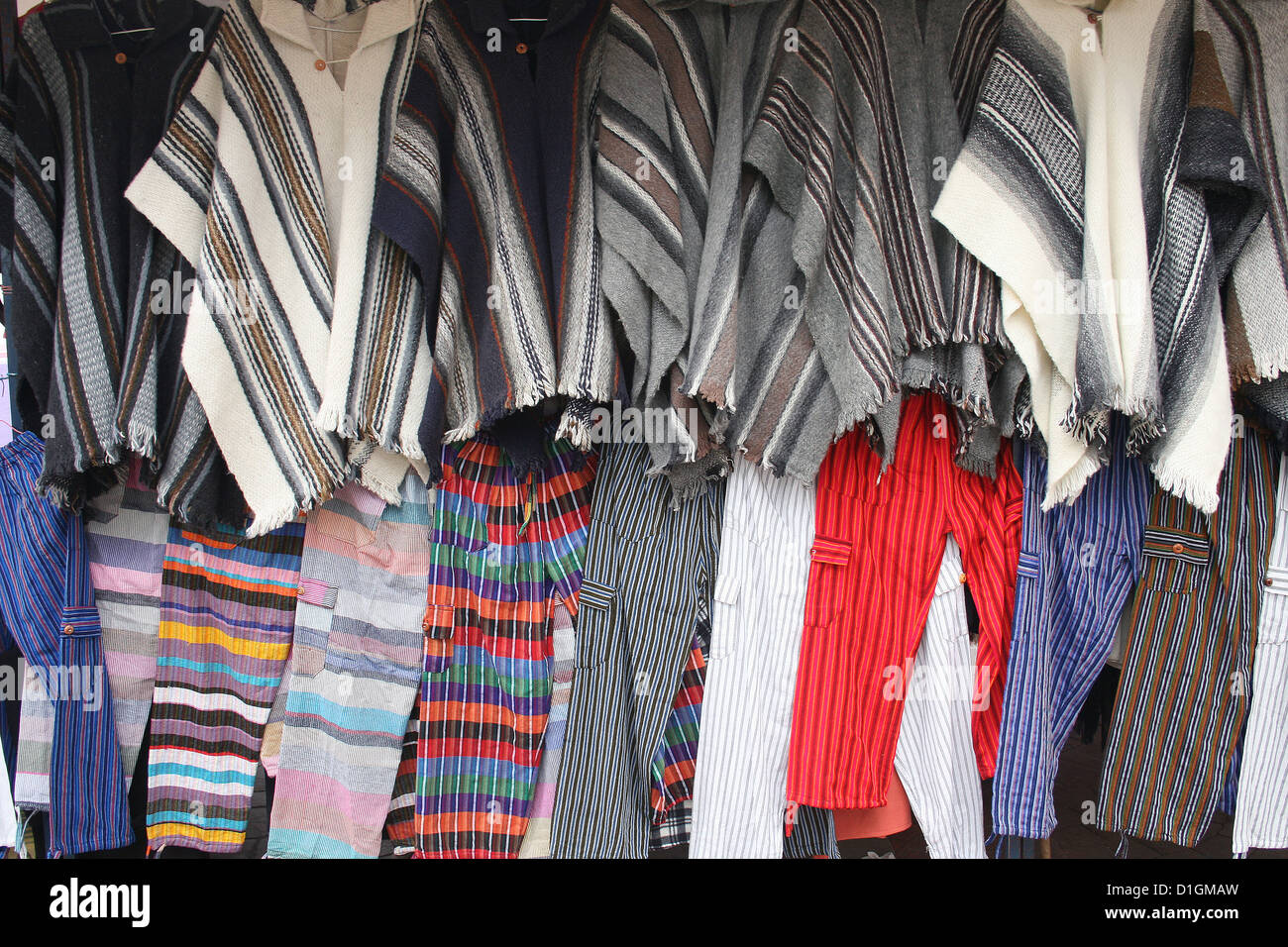 Rows of handmade colorful ponchos and pants for sale at the outdoor craft market in Cotacachi, Ecuador - Stock Image