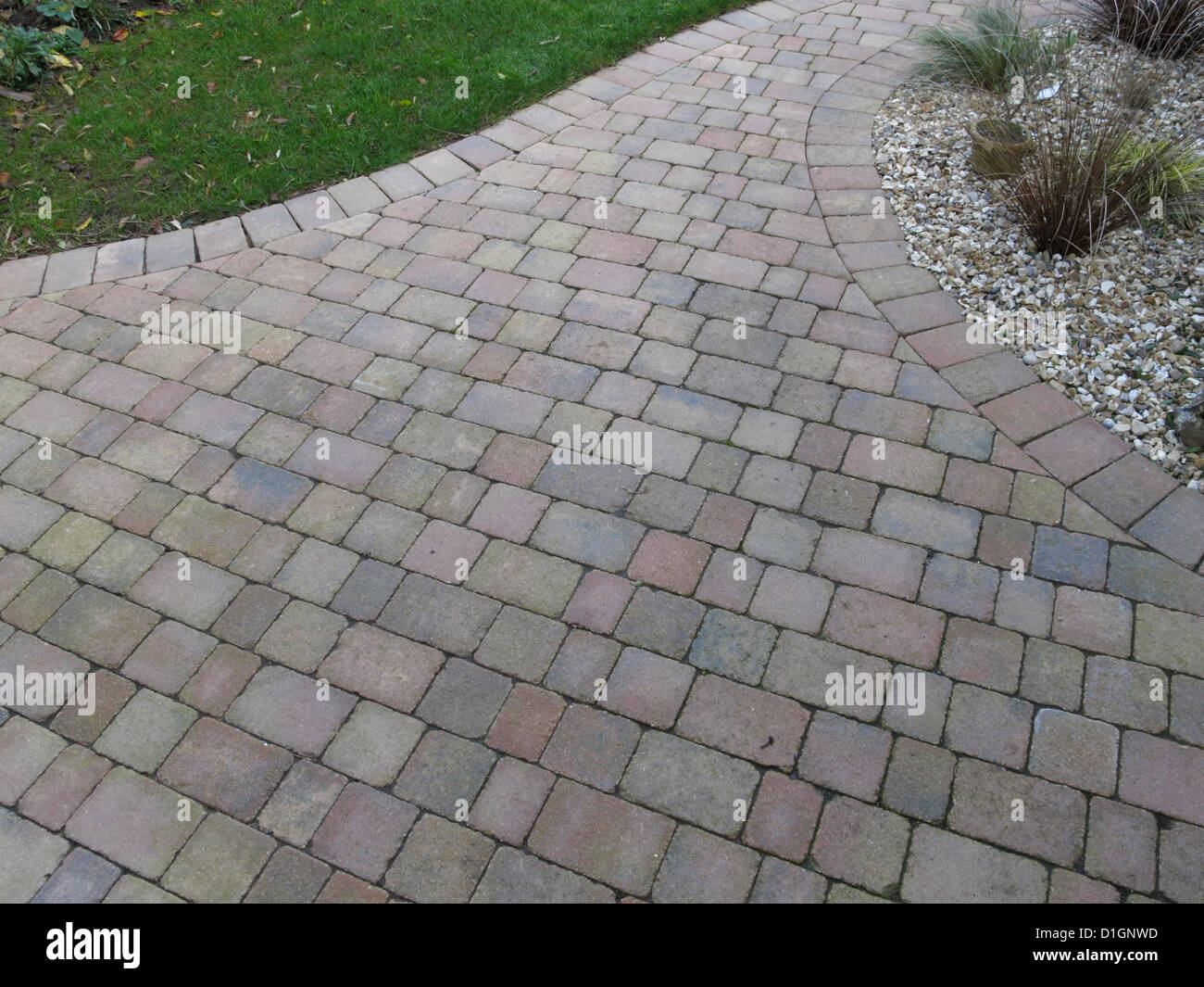 Rustic red brick patio block paving in UK garden with porous joints acting as Sustainable drainage system surface - Stock Image